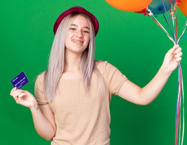 Uśmiechnięta młoda piękna dziewczyna w imprezowym kapeluszu i szelkach, trzymająca balony z kartą kredytową