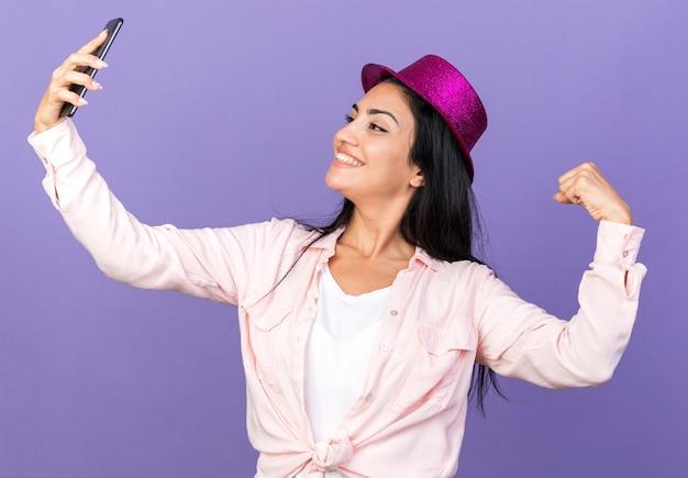 Uśmiechnięta młoda piękna dziewczyna w imprezowym kapeluszu robi selfie pokazując gest tak na niebieskiej ścianie