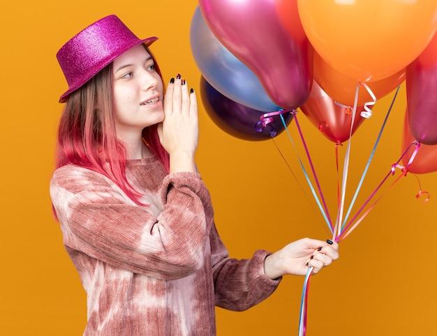 Uśmiechnięta młoda piękna dziewczyna w imprezowym kapeluszu, trzymająca balony i patrząca na kogoś, wołająca kogoś