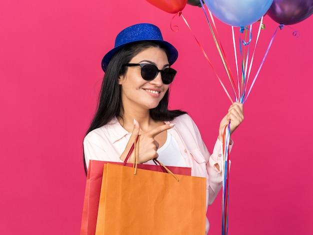 Uśmiechnięta młoda piękna dziewczyna w imprezowym kapeluszu, trzymająca balony z torbami na prezenty wskazującymi z boku