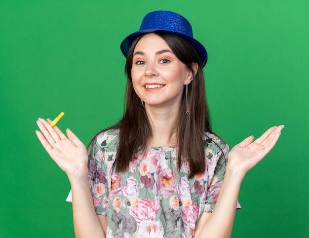 Uśmiechnięta młoda piękna dziewczyna w imprezowym kapeluszu, trzymająca gwizdek, rozkładając ręce