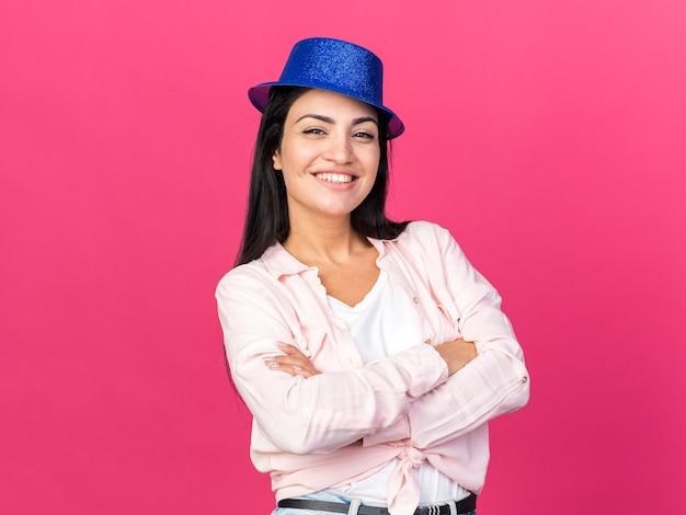 Uśmiechnięta młoda piękna dziewczyna w kapeluszu imprezowym, krzyżująca ręce izolowane na różowej ścianie