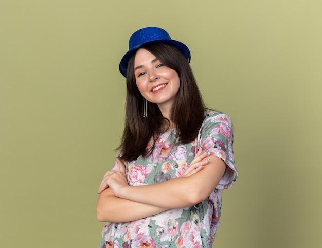 Uśmiechnięta młoda piękna dziewczyna w kapeluszu imprezowym, krzyżująca ręce