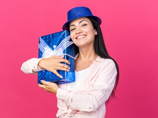 Uśmiechnięta młoda piękna dziewczyna w kapeluszu imprezowym przytuliła pudełko upominkowe