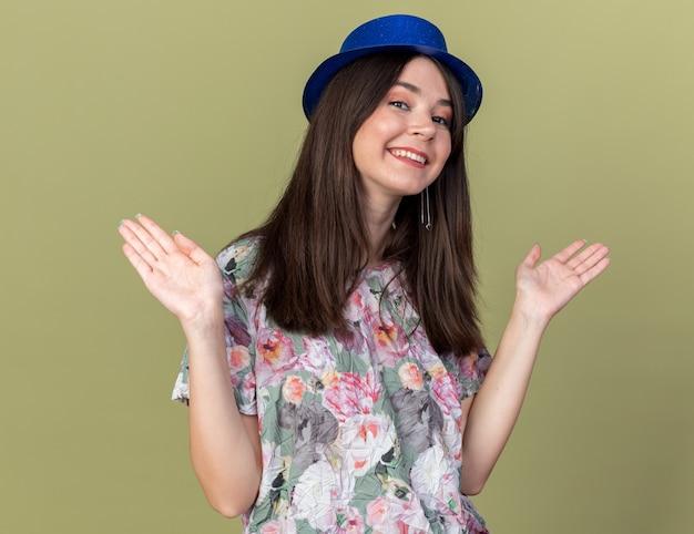 Uśmiechnięta młoda piękna dziewczyna w kapeluszu imprezowym rozkładającym ręce na oliwkowozielonej ścianie