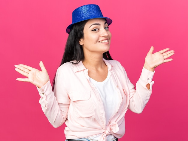 Uśmiechnięta młoda piękna dziewczyna w kapeluszu imprezowym rozkładającym ręce