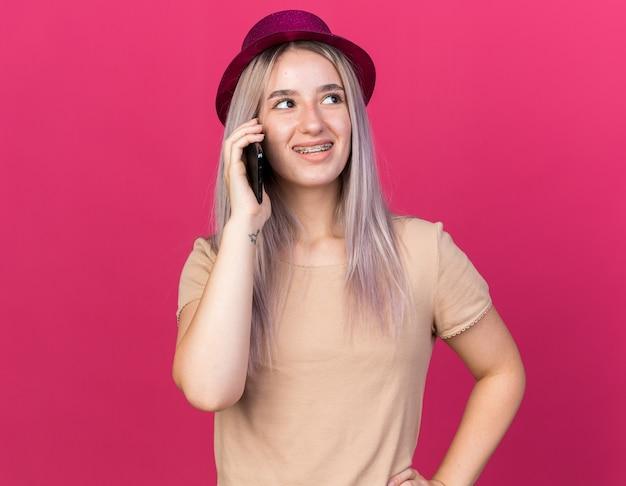 Uśmiechnięta młoda piękna dziewczyna w kapeluszu imprezowym rozmawia przez telefon