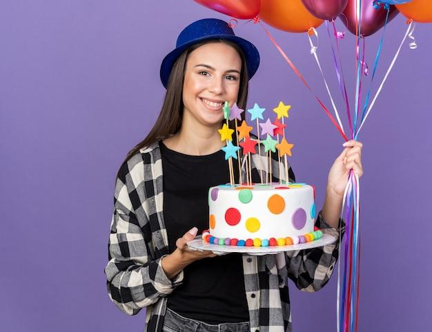 Uśmiechnięta młoda piękna dziewczyna w kapeluszu imprezowym trzymająca balony z ciastem na niebieskiej ścianie