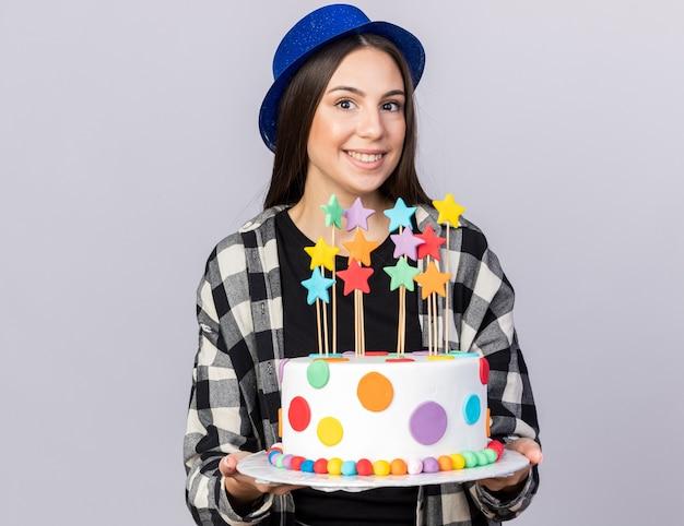 Uśmiechnięta młoda piękna dziewczyna w kapeluszu imprezowym trzymająca ciasto na białej ścianie