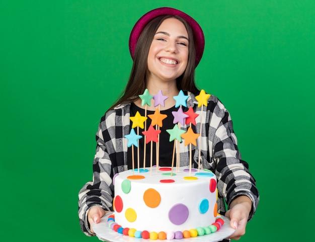 Uśmiechnięta młoda piękna dziewczyna w kapeluszu imprezowym trzymająca ciasto