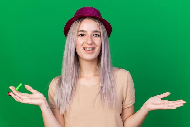 Uśmiechnięta młoda piękna dziewczyna w kapeluszu imprezowym, trzymająca gwizdek imprezowy rozkładający ręce na zielonej ścianie