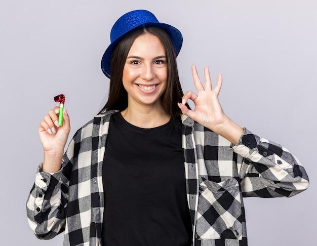 Uśmiechnięta młoda piękna dziewczyna w kapeluszu imprezowym trzymająca gwizdek pokazujący dobry gest na białej ścianie