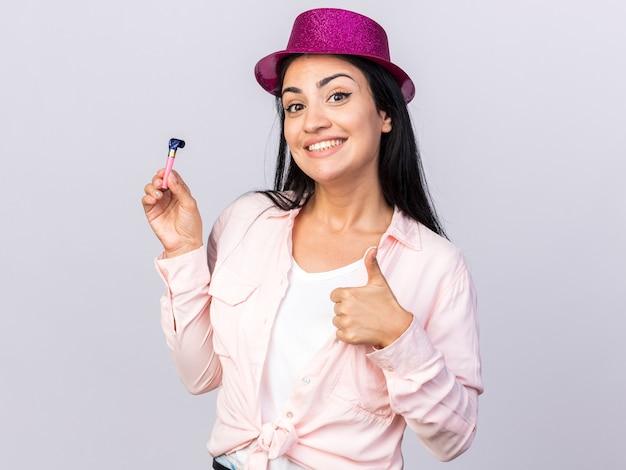 Uśmiechnięta młoda piękna dziewczyna w kapeluszu imprezowym trzymająca gwizdek pokazujący kciuk w górę