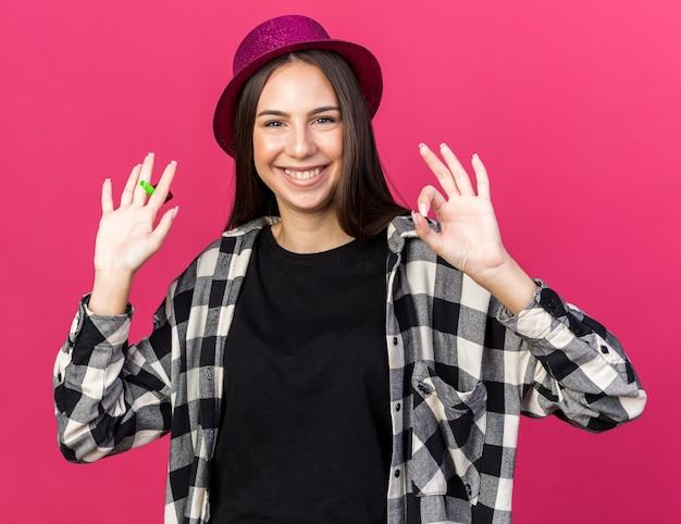 Uśmiechnięta młoda piękna dziewczyna w kapeluszu imprezowym trzymająca gwizdek pokazujący w porządku gest