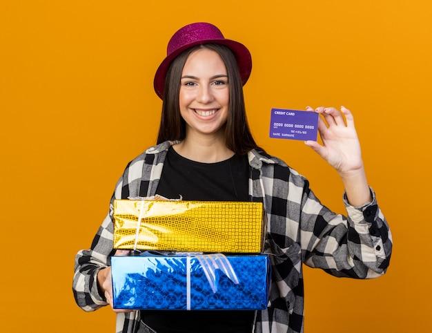 Uśmiechnięta młoda piękna dziewczyna w kapeluszu imprezowym, trzymająca pudełka na prezenty i kartę kredytową