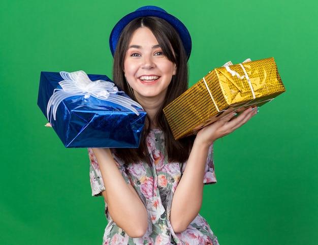 Uśmiechnięta młoda piękna dziewczyna w kapeluszu imprezowym trzymająca pudełka na prezenty