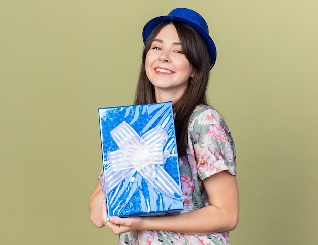 Uśmiechnięta młoda piękna dziewczyna w kapeluszu imprezowym trzymająca pudełko na prezent