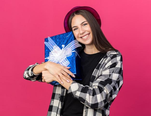 Uśmiechnięta młoda piękna dziewczyna w kapeluszu imprezowym trzymająca pudełko przytulone pudełko na prezent na różowej ścianie