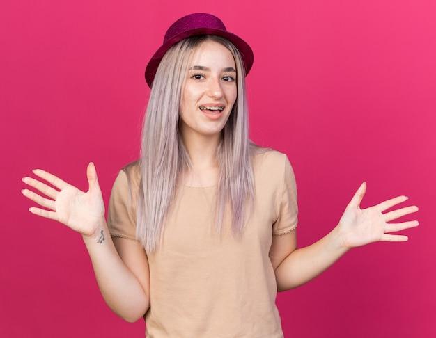 Uśmiechnięta młoda piękna dziewczyna w kapeluszu imprezowym z aparatami ortodontycznymi rozkładającymi ręce