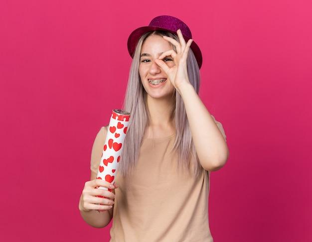 Uśmiechnięta młoda piękna dziewczyna w kapeluszu imprezowym z aparatami ortodontycznymi, trzymająca armatę konfetti pokazującą gest