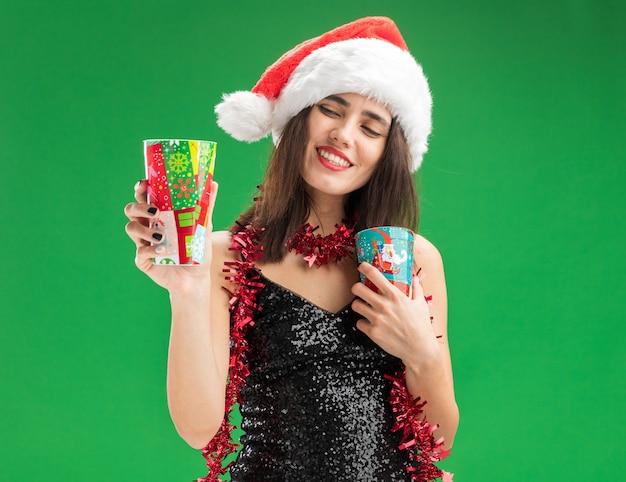 Uśmiechnięta młoda piękna dziewczyna w świątecznym kapeluszu z girlandą na szyi, trzymająca i patrząca na świąteczne kubki odizolowane na zielonym tle