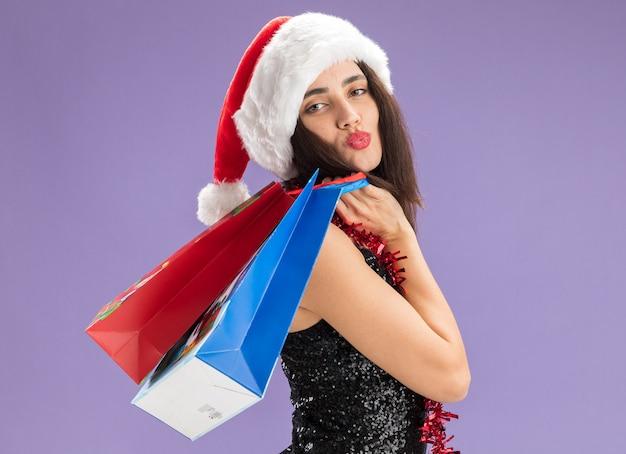 Uśmiechnięta młoda piękna dziewczyna w świątecznym kapeluszu z girlandą na szyi trzymająca torby z prezentami na ramieniu na fioletowym tle