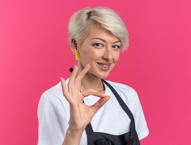 Uśmiechnięta młoda piękna kobieta fryzjerka w mundurze pokazująca dobry gest na różowym tle
