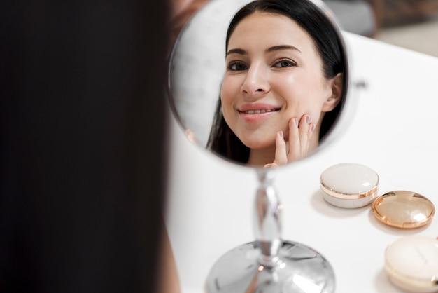 Uśmiechnięta młoda piękna kobieta patrzeje na lustrze z makeup kosmetykami ustawiającymi w domu
