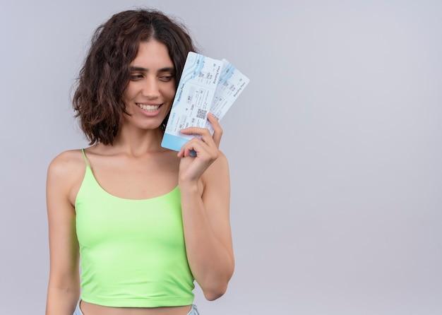 Uśmiechnięta młoda piękna kobieta trzyma bilety lotnicze na na białym tle białej ścianie z miejsca na kopię