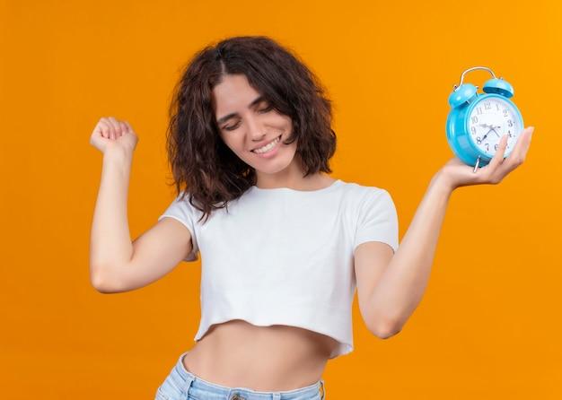 Uśmiechnięta młoda piękna kobieta trzyma budzik i podnosi pięść na odosobnionej pomarańczowej ścianie
