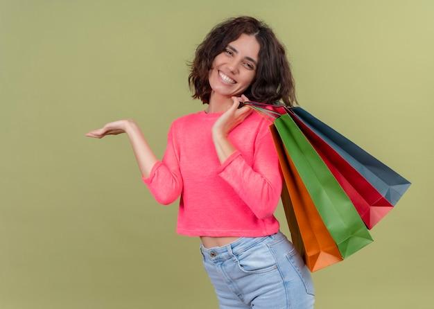 Uśmiechnięta młoda piękna kobieta trzyma papierowe torby i pokazuje pustą rękę na odosobnionej zielonej ścianie