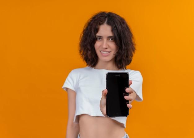 Uśmiechnięta młoda piękna kobieta trzyma telefon komórkowy i rozciągając go na pojedyncze pomarańczowe ściany z miejsca na kopię
