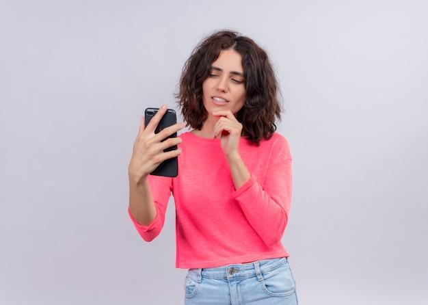 Uśmiechnięta młoda piękna kobieta trzymając telefon komórkowy i kładąc rękę na brodzie na odosobnionej białej ścianie z miejsca na kopię