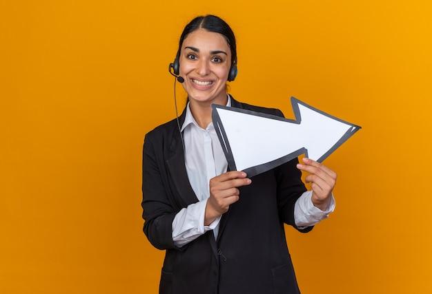 Uśmiechnięta młoda piękna kobieta ubrana w czarną marynarkę z zestawem słuchawkowym, trzymająca znak kierunkowy