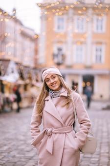 Uśmiechnięta młoda piękna kobieta w centrum europejskiego placu bożonarodzeniowego starego miasta.