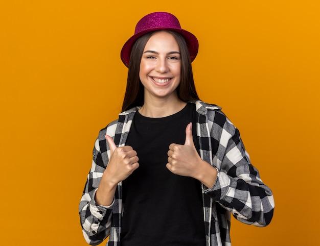 Uśmiechnięta młoda piękna kobieta w kapeluszu imprezowym pokazująca kciuk w górę