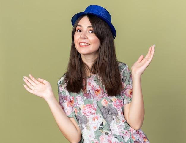Uśmiechnięta młoda piękna kobieta w kapeluszu imprezowym rozkładającym ręce na oliwkowozielonej ścianie