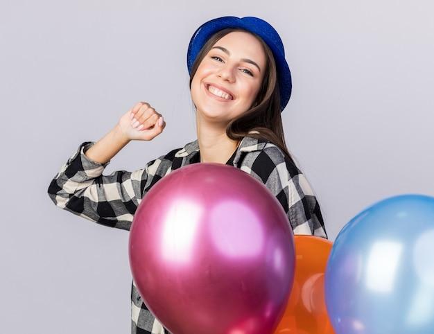 Uśmiechnięta młoda piękna kobieta w kapeluszu imprezowym trzymająca balony pokazujące gest tak na białej ścianie