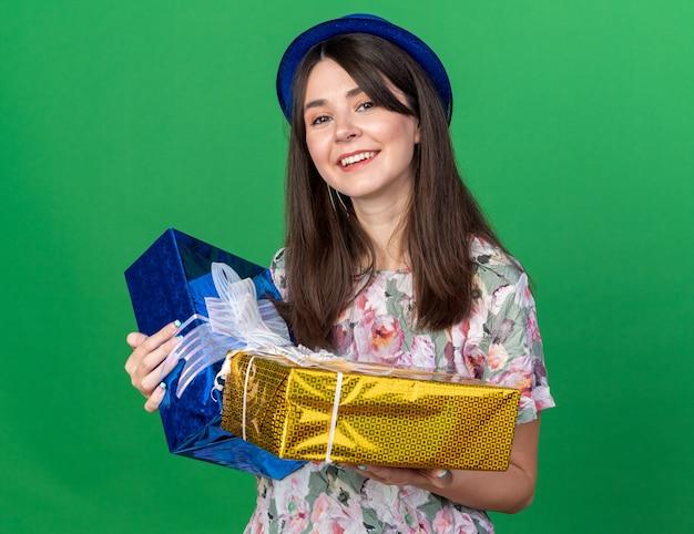 Uśmiechnięta młoda piękna kobieta w kapeluszu imprezowym trzymająca pudełka na prezenty na zielonej ścianie