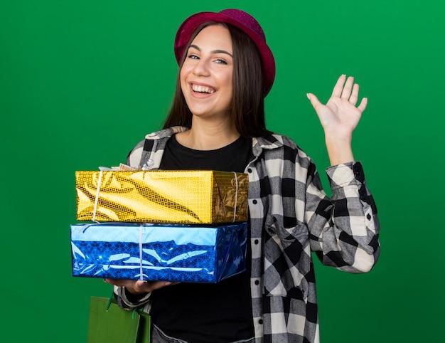 Uśmiechnięta młoda piękna kobieta w kapeluszu imprezowym trzymająca pudełka z prezentami z torbą prezentową pokazującą gest powitania na zielonej ścianie