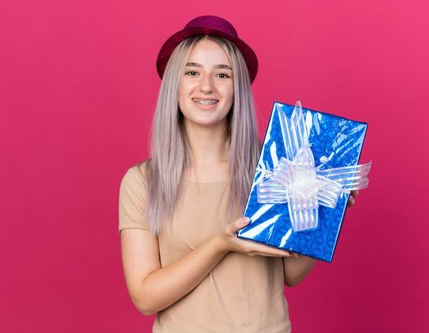 Uśmiechnięta młoda piękna kobieta w kapeluszu imprezowym trzymająca pudełko na prezent na różowej ścianie