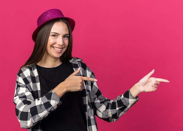 Uśmiechnięta młoda piękna kobieta w kapeluszu imprezowym wskazuje z boku na różowej ścianie z miejscem na kopię