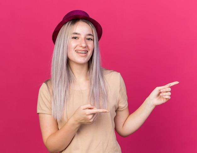 Uśmiechnięta młoda piękna kobieta w kapeluszu imprezowym z aparatami dentystycznymi wskazuje z boku na różowej ścianie