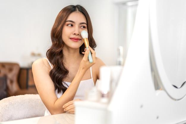 Uśmiechnięta młoda piękna ładna azjatycka kobieta czysta świeżą, zdrową białą skórę patrząc w lustro. azjatycka dziewczyna trzyma pędzle do makijażu i makijaż