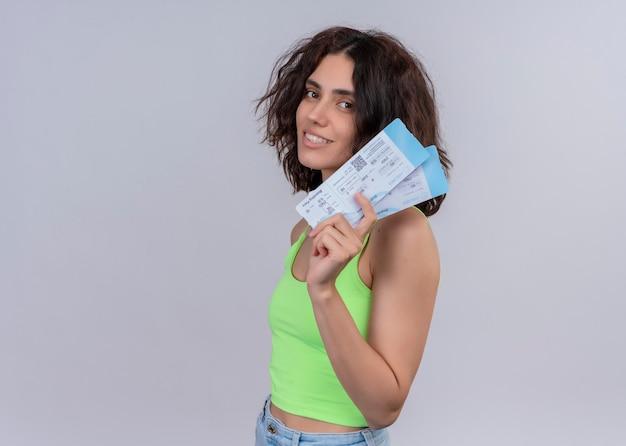 Uśmiechnięta młoda piękna podróżniczka kobieta trzyma bilety lotnicze stojąc w widoku profilu na na białym tle białej ścianie z miejsca na kopię