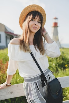 Uśmiechnięta młoda piękna stylowa kobieta, trend w modzie wiosna lato, styl boho, słomkowy kapelusz, weekend wiejski, słoneczna, czarna torebka