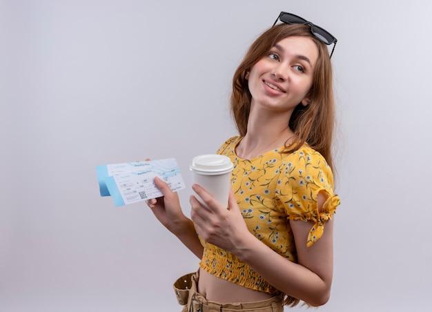 Uśmiechnięta młoda podróżnik dziewczyna nosi okulary przeciwsłoneczne na głowie trzymając bilety lotnicze i plastikową filiżankę kawy na odizolowanej białej ścianie