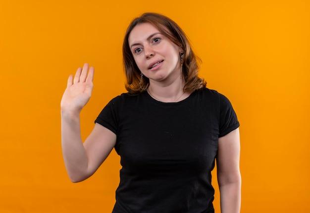 Uśmiechnięta młoda przypadkowa kobieta gestykuluje cześć na odosobnionej pomarańczowej przestrzeni