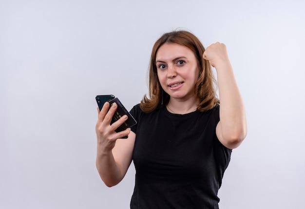 Uśmiechnięta młoda przypadkowa kobieta trzyma telefon komórkowy i podnosi pięść na odosobnionej białej przestrzeni z kopią miejsca