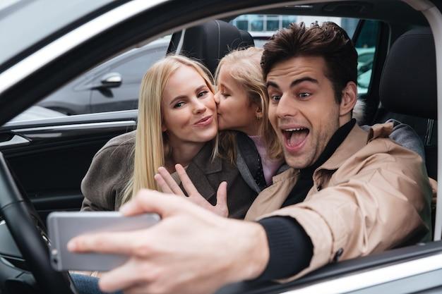 Uśmiechnięta młoda rodzina robi selfie telefonem komórkowym.